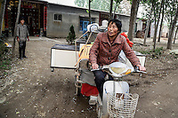 50 year old Chen Hua moves out of a village accommodation for her new urban home in Liaocheng city in the northeastern Chinese province of Shangdong. Her former village house was bulldozed by the government three years ago to make way for high-rise development. In the four years between her rural home being razed and the completion of her new city apartment, she and her family lived in temporary village housing such as this one. The Chinese government plans to move 250 million rural residents into urban areas over the coming dozen years though it is unclear whether people want to move and where the money for this project will come from. Further urbanisation is meant to drive up consumption to counterbalance an export orientated economy and end subsistence farming but the drive to get people off the land is causing tens of thousands of protests each year. /Felix Features