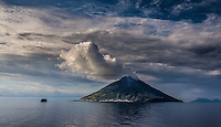 Fine Art Landscape Photograph of Mount Stromboli with dramatic smoke plumes rising from the mountain top. High above a small city which sits at the base of this active volcanic  mountain.