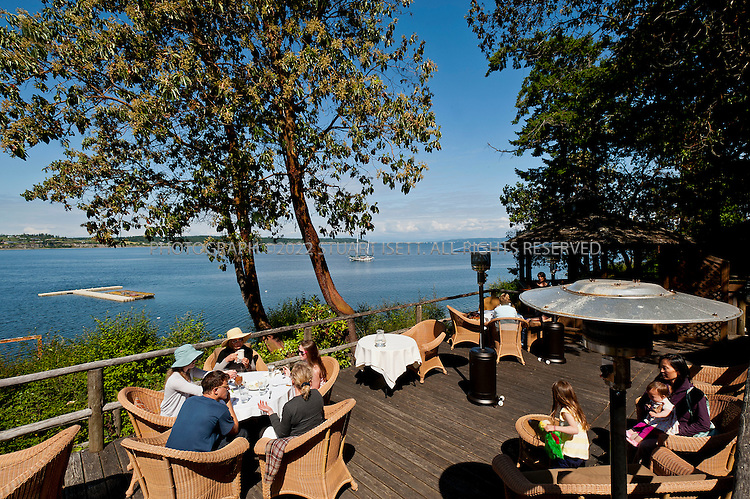 6/11/2011--Coupevill, WA, USA...The Captain Whidbey Inn, on Penn Cove on Whidbey Island. The Captain Whidbey Inn is a 102 year old establishment listed on the National Register of Historic Places. The inn is located on Whidbey Island at the west end of Penn Cove just outside Coupeville, Washington...Captain Whidbey Inn was built in the fall and winter of 1906 from Madrona logs and stone found on-site by Chris Fisher and his son Edward. The post and beam construction, with the log infill, sits intact as originally built. Larry Fisher, Chris Fisher's great-grandson, still works occasionally on the inn. It was opened in May 1907 as part of a large recreation retreat then-called Still Park. The inn and park were developed by Judge Lester Still. The park also had camping, cabins, horse trails, tennis courts and a warm salt water swimming pool. A collection of pictures from that period remain in a history collection at the inn...The inn originally contained 15 sleeping rooms upstairs and a large gathering room downstairs with a two sided fire place. The fireplace was faced with native stone; it still forms the central meeting place for the inn. Daily steamers from both Seattle and Everett were the original links to the outside world bringing passengers, supplies and mail to the dock located at the eastward-facing front of the inn. Parts of the original dock and stone stairway can still be seen while walking the current pier. Automobile access was available via ferry before Deception Pass Bridge was completed in 1935; Judge Still is credited with bringing the first automobile to Whidbey Island. The vehicle can still be seen at the Island County Historical Society Museum. Over time, the Inn has variously served as a general store, girl's school, and post office. The property returned to offering accommodations open to the public in 1946....Today, the inn appears very similar to the way it was when it was built. The original wood floors are still visible in both the lobby an