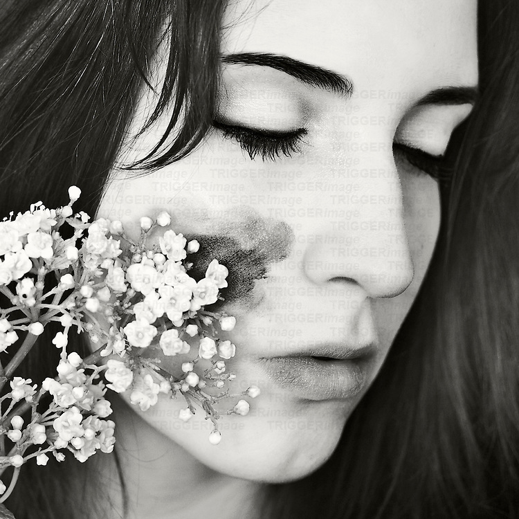 Close-up portrait of a young woman with pale skin and dark hair, with her eyes closed and her cheek stained by white little flowers.