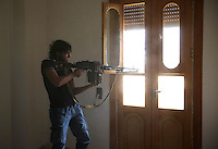 Photographer: Rick Findler..07.10.12 A soldier fighting for the Free Syrian Army fires at members of Assad's army from an abandoned house on the sixth floor of a building in the city of Aleppo, Syria.