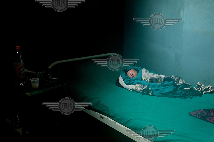 A newborn baby boy lies on a bed at the public maternity hospital. A state program has been instigated to enable women to have hospital births instead of home births and thereby reduce infant and maternal mortality rates at birth.