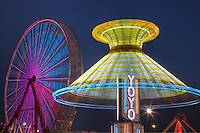 AUGUSTA, NJ - AUGUST 13: The colorfully illuminated Yo Yo spins in front of the Gentle Giant Ferris Wheel against the night sky during the New Jersey State Fair on August 13, 2010 at the Sussex County Fairgrounds, Augusta, New Jersey.