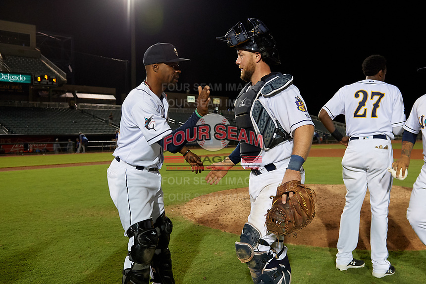 New Orleans Baby Cakes catchers Wilkin Castillo (left) and Bryan Holaday (28) celebrate after a Pacific Coast League game against the Oklahoma City Dodgers on May 6, 2019 at Shrine on Airline in New Orleans, Louisiana.  New Orleans defeated Oklahoma City 4-0.  (Mike Janes/Four Seam Images)