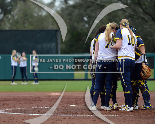 Michigan Wolverines players meet in between innings during the season opener against the Florida Gators on February 8, 2014 at the USF Softball Stadium in Tampa, Florida.  Florida defeated Michigan 9-4 in extra innings.  (Copyright Mike Janes Photography)