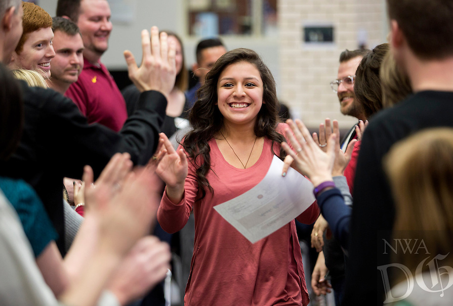 NWA Democrat-Gazette/JASON IVESTER<br /> Anahi (cq) Garcia, Lakeside Jr High ninth-grader, makes her way through a &quot;high-five&quot; line of faculty members on Thursday, Feb. 18, 2016, after receiving her certificate in an Eglish as a Second Language exit ceremony at the Springdale school. Twelve students were recognized for exiting the ESL program.