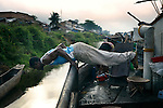 BUMBA, DEMOCRATIC REPUBLIC OF CONGO MARCH 29: Richard Makeleka, age 26, a crew members, keeps in shape during free time on a boat with destination Kinshasa on March 29 2006 in Bumba, Congo, DRC. He works with many other young crewmembers without any training. Passengers usually sleep in the open, often on top of maize bags or other cargo. The boat carries many animals such as pigs, goats, crocodiles, monkeys, lizards, etc. The Congo River is a lifeline for millions of people, who depend on it for transport and trade. The journey from Kisangani to Kinshasa is about 1750 kilometers, and it takes from 3-7 weeks on the river, depending on the boat. During the Mobuto era, big boats run by the state company ONATRA dominated the traffic on the river. These boats had cabins and restaurants etc. All the boats are now private and are mainly barges that transport goods. The crews sell tickets to passengers who travel in very bad conditions, mixing passengers with animals, goods and only about two toilets for five hundred passengers. The conditions on the boats often resemble conditions in a refugee camp. Congo is planning to hold general elections by July 2006, the first democratic elections in forty years. (Photo by Per-Anders Pettersson)