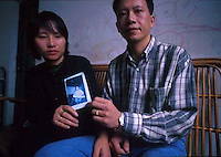 Au Ming Cheung (right) and his wife Yam Chau Chi hold a picture of their son Kam Chiu who was stolen from outside their home in shenzhen south China.  China's One child policy and the whole nations craving for boys has resulted in a valuable trade in the highly prized young boys.  As well as boys being stolen and sold into the coutry-side, the policy has resulted in a massive inbalance in the sexes with sometimes more than wtice as many boys as girls in some areas of China.