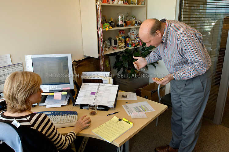 1/23/2006--Redmond, WA, USA..10:45 AM: Carrying a hand full of peanuts he took for a co-worker's office, Steve Ballmer, CEO of Microsoft, checks out his day's schedule with his executive assistant Debbie Hill...Photograph ©2007 Stuart Isett.All rights reserved