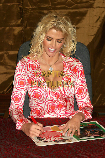 ANNA NICOLE SMITH.Signs autographs at the re-launch of The National Enquirer Hudson News in Grand Central Station, New York City, USA, April 7th 2005..half length boobs cleavage silver cross necklace signing magazine.Ref: IW.www.capitalpictures.com.sales@capitalpictures.com.©Ian Wilson/Capital Pictures.