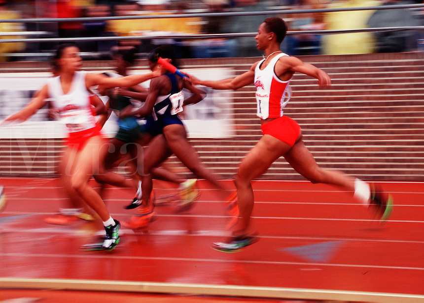 Blurred action image of female relay runners at a track meet as they hand off a baton.
