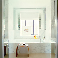 Grey-veined marble and mirrored walls in the minimalist bathroom which also has a flavour of the glamorous 30's