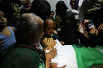 Relatives of Palestinian Abdul Fattah Abu Azoum 17, who was killed in Israeli tank fire earlier in the day, at the Israel-Gaza border, mourn over his body during his funeral in Rafah in the southern Gaza strip on June 28, 2018. Photo by Ashraf Amra