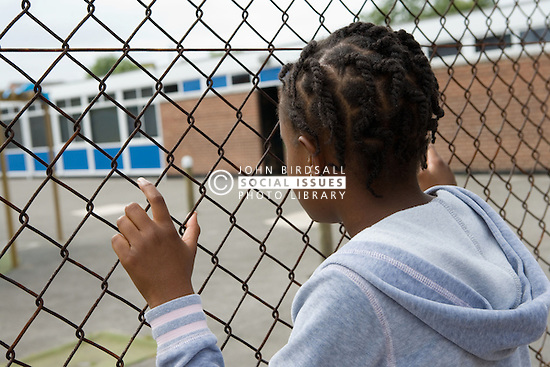 Young girl looking through fence into school playground,