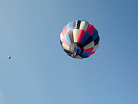 A hopper balloon carrying a single man  rises into the sky lifted by hot air from propane burners, British School of ballooning, Ebernoe, West Sussex.
