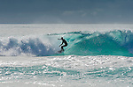 A lone surfer rides a wave at Friendly Beaches on the east coast of Tasmania in Australia.