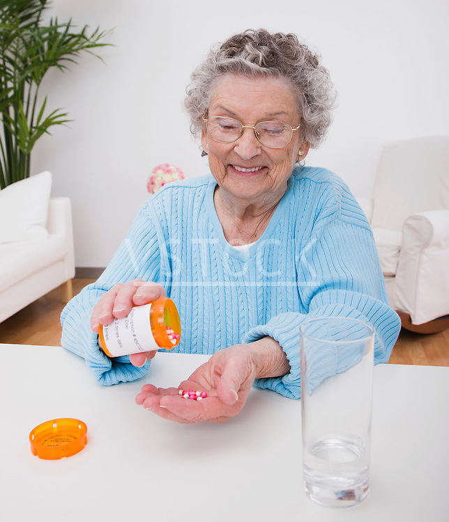 Smiling senior woman pouring pills into hand