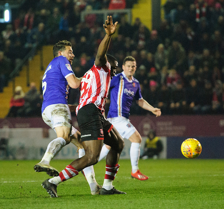 Lincoln City's John Akinde is tackled by Exeter City's Aaron Martin, but his appeals for a penalty were rejected<br /> <br /> Photographer Chris Vaughan/CameraSport<br /> <br /> The EFL Sky Bet League Two - Lincoln City v Exeter City - Tuesday 26th February 2019 - Sincil Bank - Lincoln<br /> <br /> World Copyright © 2019 CameraSport. All rights reserved. 43 Linden Ave. Countesthorpe. Leicester. England. LE8 5PG - Tel: +44 (0) 116 277 4147 - admin@camerasport.com - www.camerasport.com