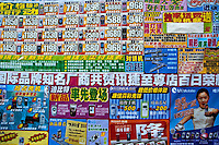 Colourful posters advertising consumer electronics and mobile phones in the street, Xi'an, Shaanxi, China.