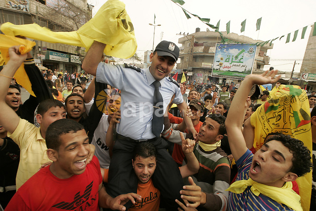 A Palestinian Hamas policeman holds the Fatah flag as he joins celebrations marking the political reconciliation agreement during a rally in Rafah, southern Gaza Strip, on May 4, 2011 as Palestinians in the West Bank and Gaza Strip gather to welcome a reconciliation deal signed by rival movements Hamas and Fatah in Cairo. Photo by Abed Rahim Khatib