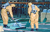 Firefighters wearing breathing apparatus and chemical protection suits attending a chemical spillage in a large factory. They are using an absorbent powder to soak up the chemical. This image may only be used to portray the subject in a positive manner..©shoutpictures.com..john@shoutpictures.com