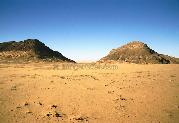 Africa, Libya, Fezzan. The Gebel Sherif mountains southwest of Kufra where during Second World War on January 31 1941 the Long Range Desert Group was attacked by the Italian Compagnie Sahariane. Libyen 1999/2000. --- INFO: The Long Range Desert Group (LRDG) was a reconnaissance and raiding unit of the British Army during the Second World War. Originally called the Long Range Patrol Unit (LRP), the unit was founded in Egypt in June 1940 by Major Ralph A. Bagnold. Bagnold was assisted by Captain Patrick Clayton and Captain William Shaw. At first the majority of the men were from New Zealand, but they were soon joined by Rhodesian and British volunteers, whereupon new sub-units were formed and the name was changed to the better-known Long Range Desert Group (LRDG). The LRDG vehicles were mainly two wheel drive, chosen because they were lighter and used less fuel than four wheel drive. They were stripped of all non-essentials, including doors, windscreens and roofs. They were fitted with a bigger radiator, a condenser system, built up leaf springs for the harsh terrain, wide, low pressure desert tyres, sand mats and channels, plus map containers and a sun compass devised by Bagnold. Wireless trucks had special compartments built into the bodywork to house wireless equipment. Initially the LRDG patrols were equipped with one CMP Ford 15 cwt F15 truck for the commander, while the rest of the patrol used up to 10 Chevrolet 30 cwt WB trucks. On 31 January 1941 'T' Patrol commanded by Captain Patrick Clayton was attacked by the Compagnia Autosahariana di Cufra, an Italian unit similar to the LRDG, in the Gebel Sherif valley south of Cufra, Libya. The LRDG had one man killed and three men captured, and three of the eleven trucks were destroyed during the battle. The Italians losses were five killed and three wounded, and one truck was abandoned.