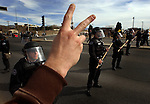 pvcpeaceprot2/3-15-03/jp2.  Dozens of APD officers suited-up in riot gear stand at the ready on Gibson Blvd. near the Truman gate entrance to Kirtland AFB as an anti-war activist flashes the peace sign from the sidewalk, Saturday March 15, 2003.  (Pat Vasquez-Cunningham/Journal)
