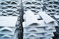 Stacks of white roofing tiles.