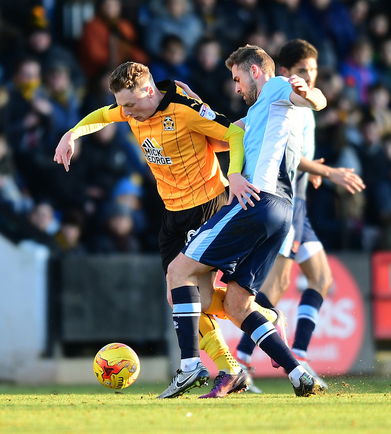 Cambridge United's George Maris is tackled by Blackpool's Clark Robertson<br /> <br /> Photographer Chris Vaughan/CameraSport<br /> <br /> The EFL Sky Bet League Two - Cambridge United v Blackpool - Saturday 14th January 2017 - The Cambs Glass Stadium - Cambridge<br /> <br /> World Copyright &copy; 2017 CameraSport. All rights reserved. 43 Linden Ave. Countesthorpe. Leicester. England. LE8 5PG - Tel: +44 (0) 116 277 4147 - admin@camerasport.com - www.camerasport.com