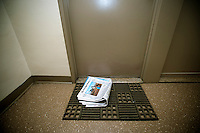 A home delivery copy of the New York Times, containing some of the Sunday sections, is seen in front of a door in an apartment building in New York on Saturday, September 17, 2011. (© Richard B. Levine)