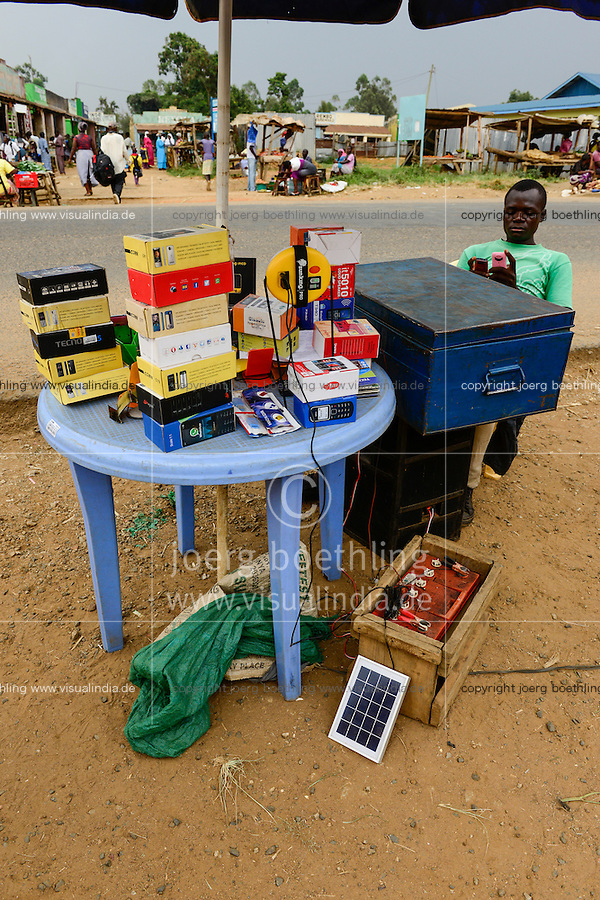 KENYA, Bukura, street vendoor selling mobile phones andre charges phones with car battery and PV module / KENIA, County Kakamega, Bukura, Markt mit Stand fuer Mobiltelefone