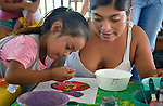 Blanca Aguilar assists her 4-year old daughter Evelyn Garcia Aguilar during an arts and crafts session of the early intervention program of Piña Palmera, a center for community based rehabilitation for people living with disabilities in Zipolite, a town in Oaxaca, Mexico. The girl is deaf.