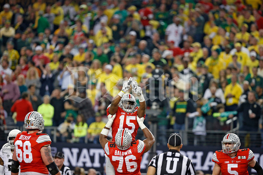 Ohio State Buckeyes offensive lineman Darryl Baldwin (76) throws Ohio State Buckeyes running back Ezekiel Elliott (15) up into the air after Elliott scored a touchdown run during the 3rd quarter in College Football Playoff Championship game at AT&T Stadium in Arlington, Texas on January 12, 2015.  (Dispatch photo by Kyle Robertson)