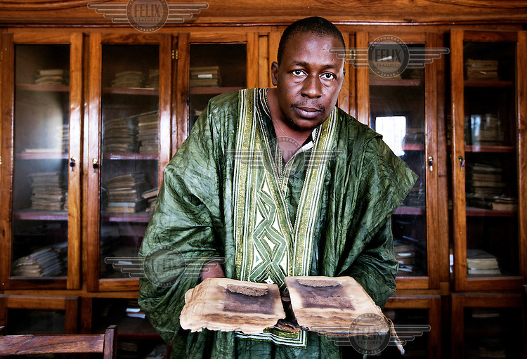 A man shows a book from a collection of antique Arabic texts.