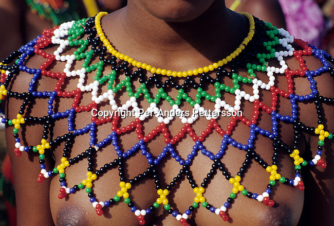 NONGOMA, SOUTH AFRICA - SEPTEMBER 11: An unidentified maiden's traditional Zulu necklace as she's preparing for the annual Reed Dance on September 11, 2004 in Nongoma in rural Natal, South Africa. About 20.000 fellow maidens from all over South Africa has arrived to dance for Zulu King Goodwill Zwelethini at the Enyokeni Royal Palace in Kwa-Nongoma about 350 kilometers from Durban. The girls come to the kingdom to declare their virginity and the ceremony encourages girls and young women to abstain from sexual activity to curb the spread of HIV-Aids. (Photo: Per-Anders Pettersson)......