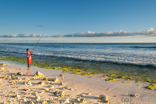 A local i-kiribati fishing from the beach on the island of Kiritimati in Kiribati