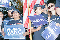 """People watch as entrepreneur and Democratic presidential candidate Andrew Yang speaks to a large crowd in Cambridge Common near Harvard Square in Cambridge, Massachusetts, on Mon., September 16, 2019. Yang's unlikely presidential bid is centered on his idea for a """"Freedom dividend,"""" which would give USD$1000 per month to every adult in the United States. After appearing in three Democratic party debates, Yang has risen in polls from longshot candidate to within the top 10.   In the picture, people can be seen holding MATH signs or wearing hats that say MATH. The slogan MATH is now said to mean """"Make America Think Harder"""" and the candidate frequently sites statistics and mathematics in his speeches."""