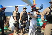 A Sailor assigned to the guided-missile destroyer USS Kidd's (DDG 100) visit, board, search and seizure team greets a crew member of the Iranian-flagged fishing dhow Al Molai in the Arabian Sea, Friday, January 6, 2012. Kidd's visit, board, search and seizure team detained 15 suspected pirates, who were holding a 13-member Iranian crew hostage for several weeks, according to the members of the crew. Kidd is conducting counter-piracy and maritime security operations while deployed to the U.S. 5th Fleet area of responsibility. .Credit: U.S. Navy via CNP