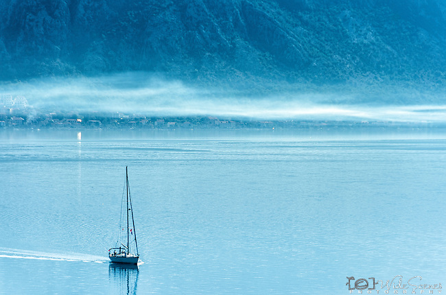 Yacht sailing through mist on bay of Kotor, Montenegro