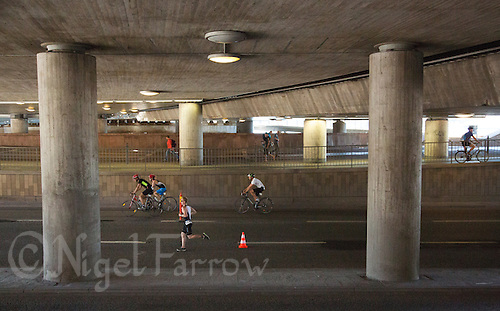 25 AUG 2013 - STOCKHOLM, SWE - Competitor cycle and run under a railway bridge during the Stockholm Triathlon in Stockholm, Sweden (PHOTO COPYRIGHT © 2013 NIGEL FARROW, ALL RIGHTS RESERVED)