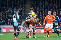 Sido Jombati of Wycombe Wanderers battles Craig Mackail-Smith of Luton Town for the ball during the Sky Bet League 2 match between Wycombe Wanderers and Luton Town at Adams Park, High Wycombe, England on 6 February 2016. Photo by Andy Rowland.
