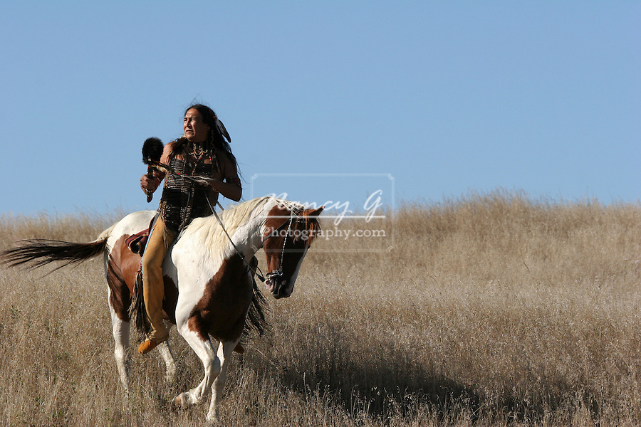 A Native American Indian riding horseback looking for ememies through the prairie of South Dakota