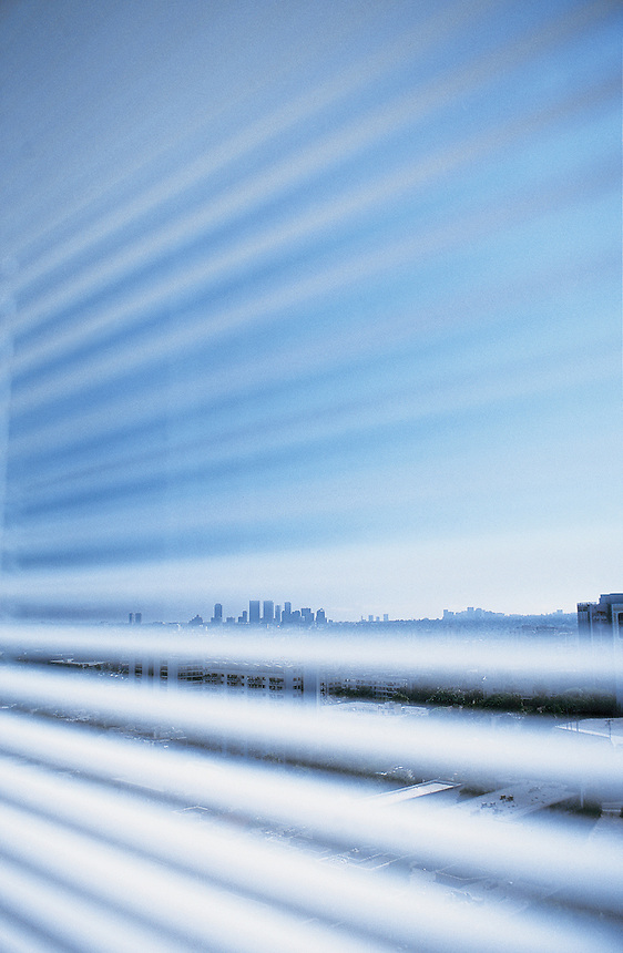 View of Los Angeles through the blinds of a room at the luxury hotel Mondrian, designed by Philippe Stark. LA 08-02