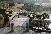 Stone bridges and gravel pathways wind around the ornamental lake at Suizen-ji garden