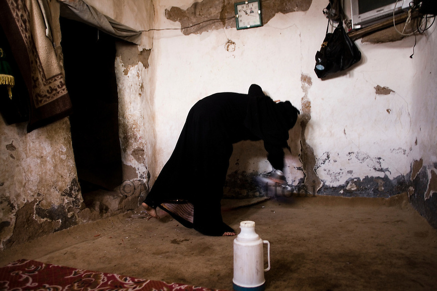 Yemen - Sana'a - Fatima, 34 years old cleaning the house. Fatima is pregnant and collects water one a day from the water pump that belongs to a few family, each family has a limited access to water according how much they pay, Fatima has to walk one hour everyday to collect the water and usually brings back 3/4 litres per day. Yemen's economy depends heavily on oil production, and its government receives the vast majority of its revenue from oil taxes. Yet analysts predict that the country's petroleum output, which has declined over the last seven years, will fall to zero by 2017. The government has done little to plan for its post-oil future. Yemen's population, already the poorest on the Arabian peninsula and with an unemployment rate of 35%, is expected to double by 2035..The trends will exacerbate large and growing environmental problems, including the exhaustion of Yemen's groundwater resources. Given that a full 90% of the country's water is used for agriculture, this trend portends disaster..Sanaa's well are expected to dry out by 2015, partly due to illegal drilling, partly because 40% of the city's water is diverted for qat production, and partly because conservation rules are difficult to enforce. Only 20% of the houses receive water, the other 80% has to collect it from pumps and wells. 15% of the urban population only uses bottled water as its primary drinking water source and that is why Yemen has one of the highest world mortality rate, most of the diseases being related to water..