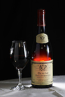 A bottle of Maison Louis Jadot Beaune Boucherottes 2002 red burgundy wine and a glass of red wine standing on a table top with a white cloth. Backlit backlight back light lit Black background, Maison Louis Jadot, Beaune Côte Cote d Or Bourgogne Burgundy Burgundian France French Europe European