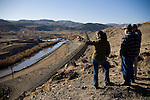 Patti Bakker, left, of The Nature Conservancy, Greg Dennis, center, and Mark Struble, right, og the Bureau of Land Management watch as the Truckee River is diverted back to its original course, on the far side, on December 2, 2009 in Mustang, NV.