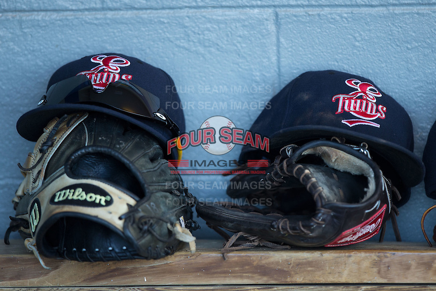 A pair of Elizabethton Twins hats sit on top of gloves in the visitors dugout during the game against the Kingsport Mets at Hunter Wright Stadium on July 9, 2015 in Kingsport, Tennessee.  The Twins defeated the Mets 9-7 in 11 innings. (Brian Westerholt/Four Seam Images)