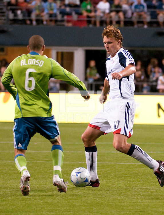 Edgaras Jankauskas (l) of the New England Revolution works the ball against Osvaldo Alonso (6) of the Seattle Sounders in the match at the XBox Pitch at Quest Field on August 20, 2009. The Revolution defeated the Sounders 1-0.