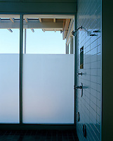 The lower two-thirds of a glass wall in the shower room  have been sandblasted for privacy whilst affording access to the view